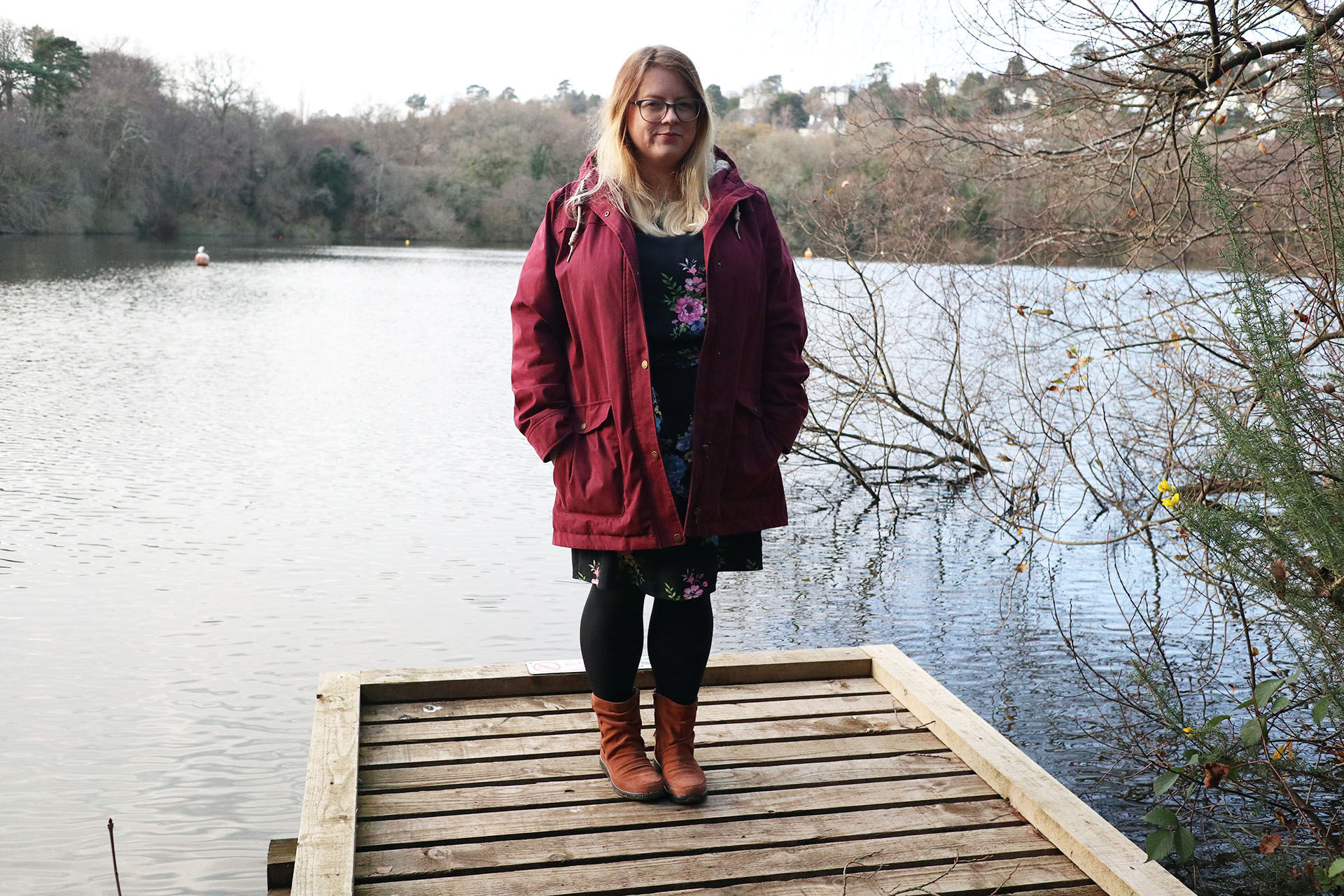 Standing near a lake wearing a red coat and a pair of Pixie boots from Hotter Shoes