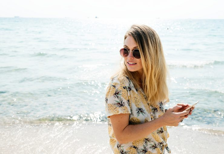 How to declutter your digital life - woman on beach holding phone and smiling, feeling calm and happy