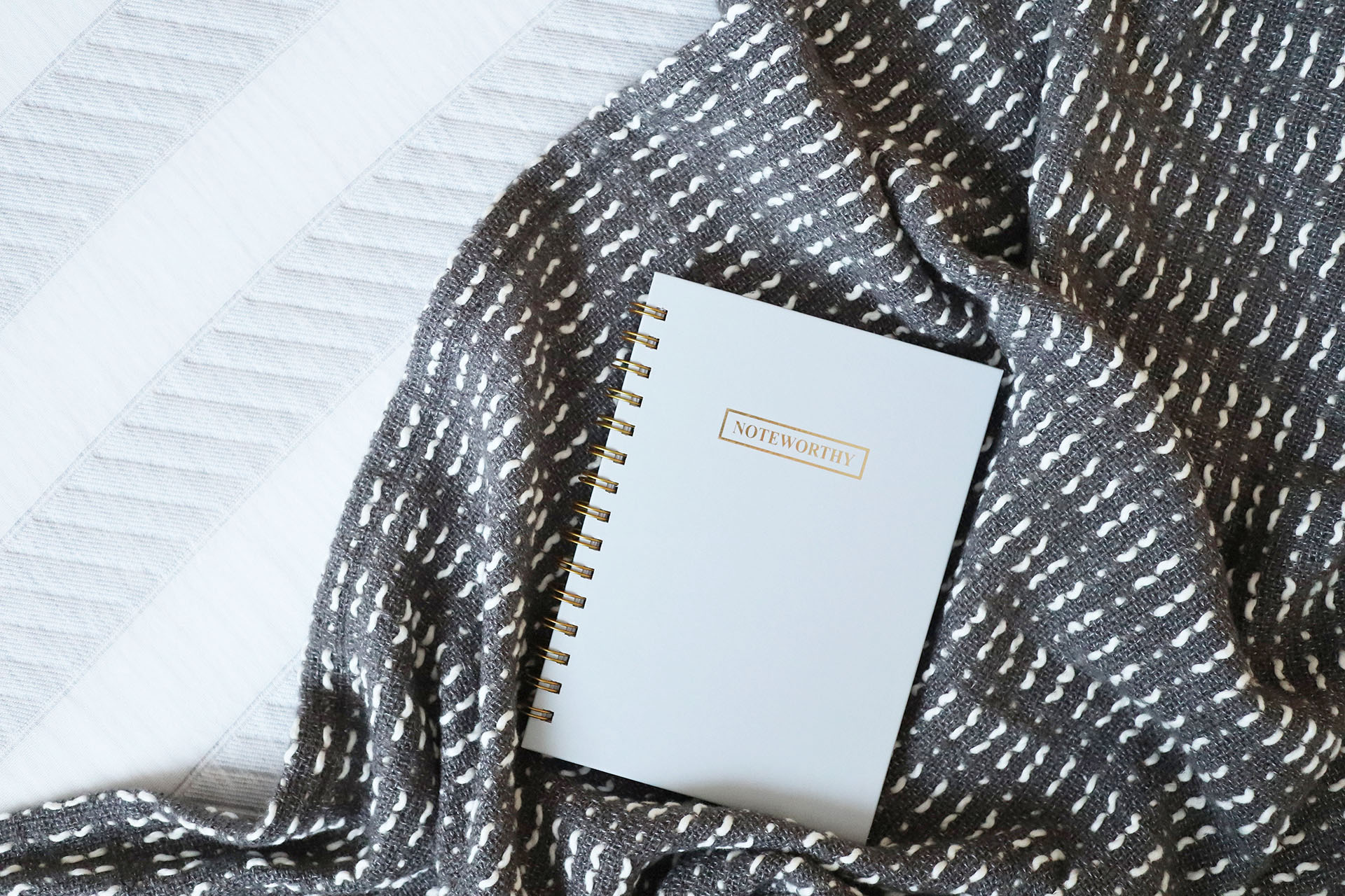 A notebook and throw placed on top of the Leesa mattress, with the Leesa stripes visible