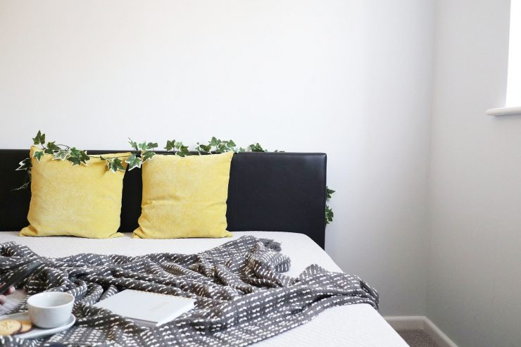 Bed featuring a Leesa mattress, made up with cushions and a throw