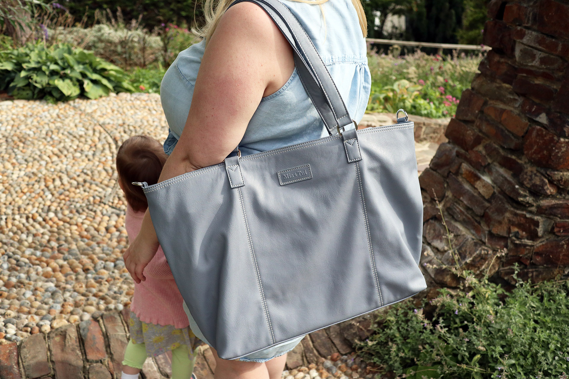 The Mia Tui Jennie, worn as a shoulder bag on a family day out