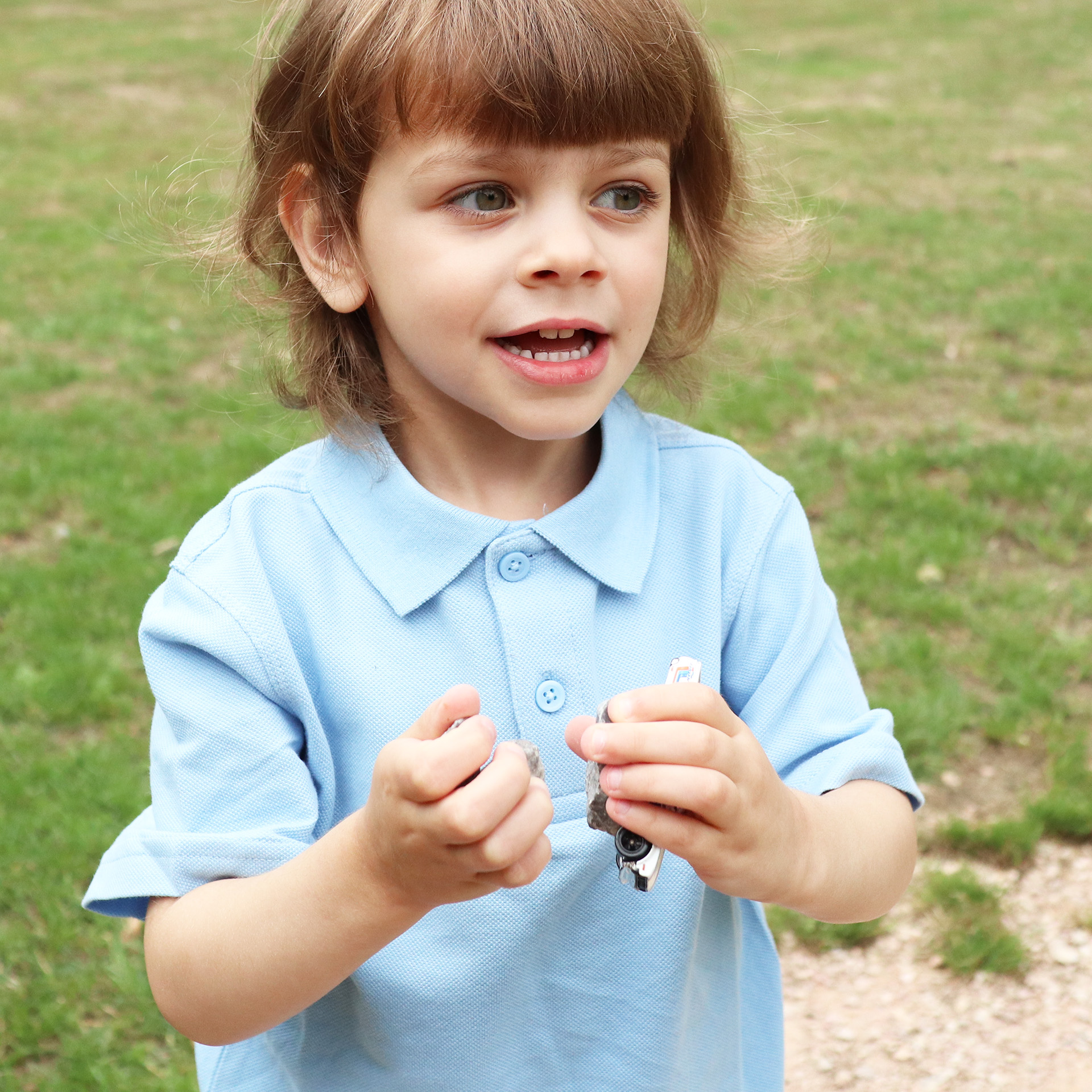 Child in school uniform playing with cars outdoors